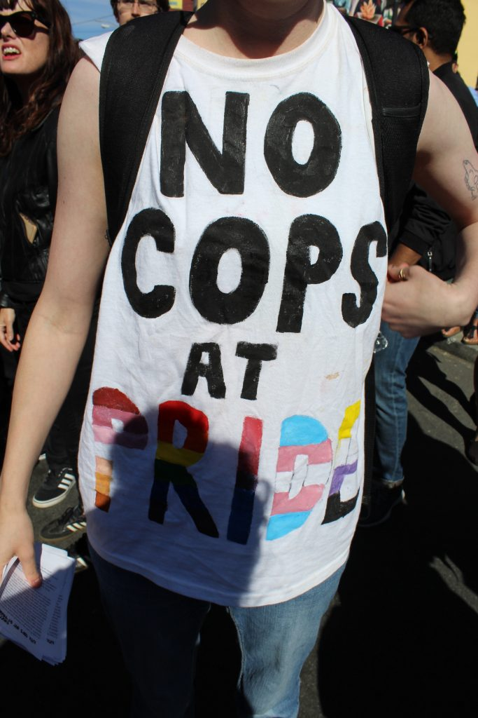 """person wearing a tshirt that reads """"no cops at pride"""""""
