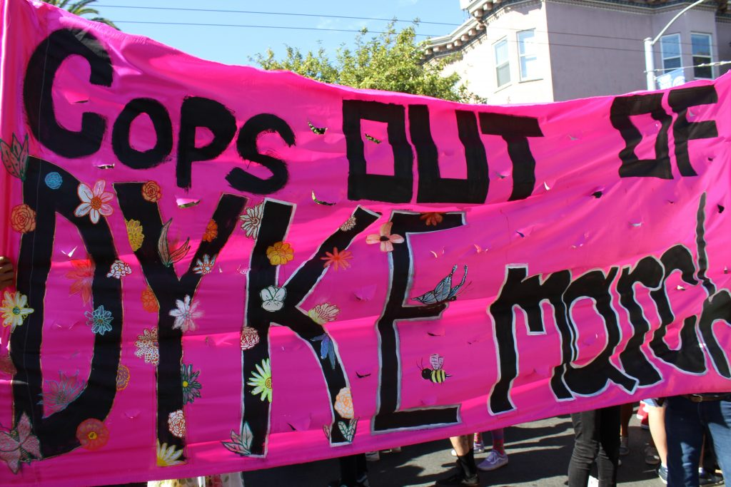 "a pink banner reading ""cops out of dyke march"""