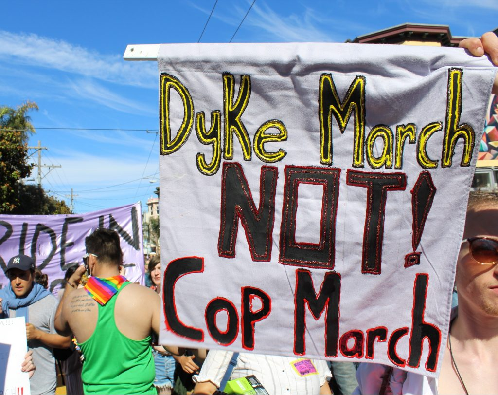 "person holding a banner that says ""dyke march no cop march"""