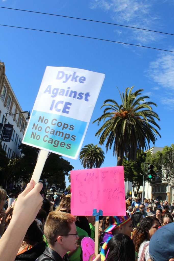 "people gather at the intersection and a sign is visible reading ""dyke against ice --- no cops no camps no cages"""