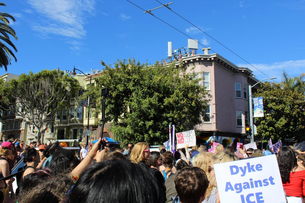 """people gather at the intersection and a sign is visible reading """"dyke against ice --- no cops no camps no cages"""""""