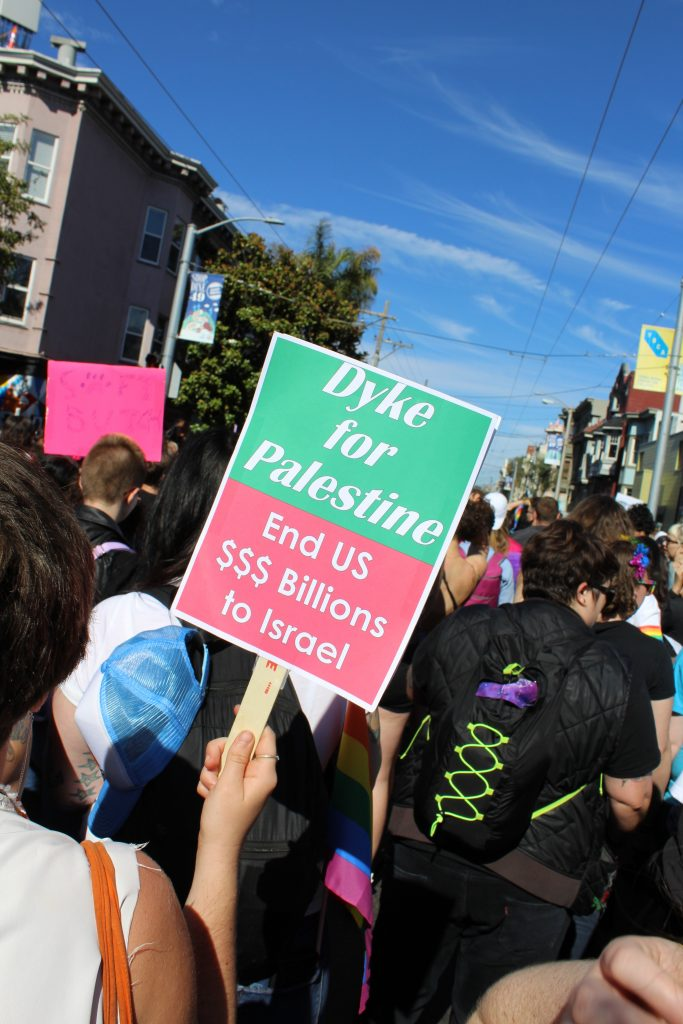 """people start to march and someone holding a sign reading """"dyke for palestine -- end US $$$ billions to israel"""""""