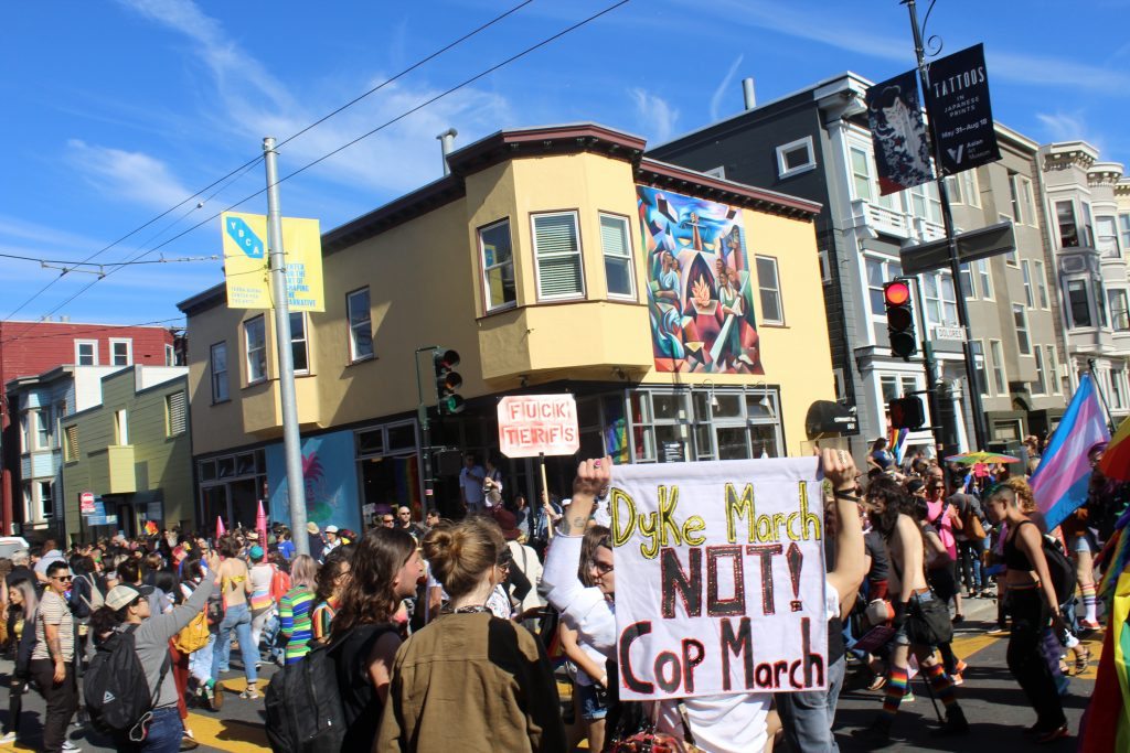 "people stand around as the dyke march begins to pass and someone is holding a sign reading ""dyke march not cop march"""