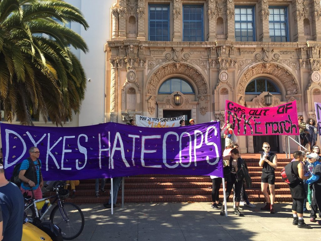 "people gathering on the steps of mission high with banners reading ""dykes hate cops"" and ""cops out of dyke march"""