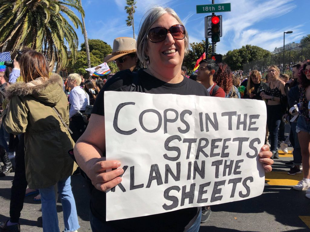 "person at the intersection of 18th and dolores holding a sign reading ""cops in the streets --- klan in the sheets"""