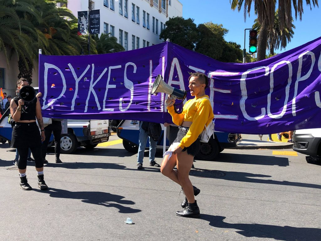 """two people with megaphones in front of a banner at 18th and dolores that reads """"dykes hate cops"""""""