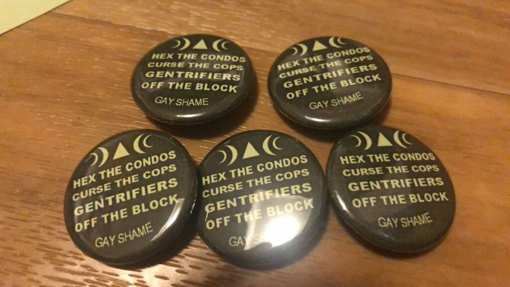 """Five buttons on a woodgrain table that read """"Hex the condos, curse the cops, gentrifiers off the block gay shame"""" in yellow font on a black background."""